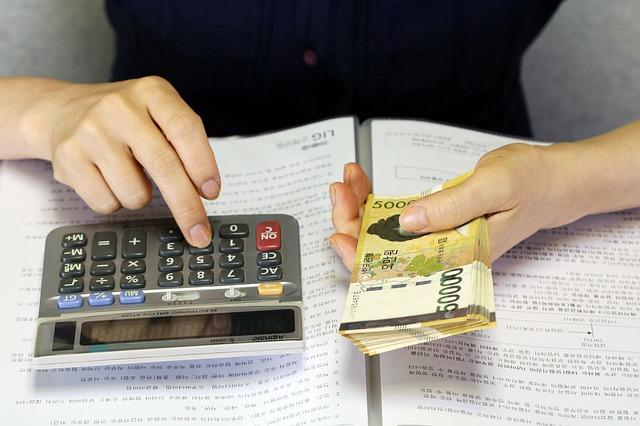 žena držící balíček peněz a počítající na kalkulačce