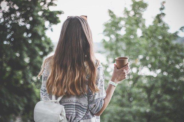 žena s batohem a kávou