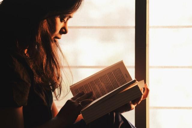 brunetka s knihou u okna